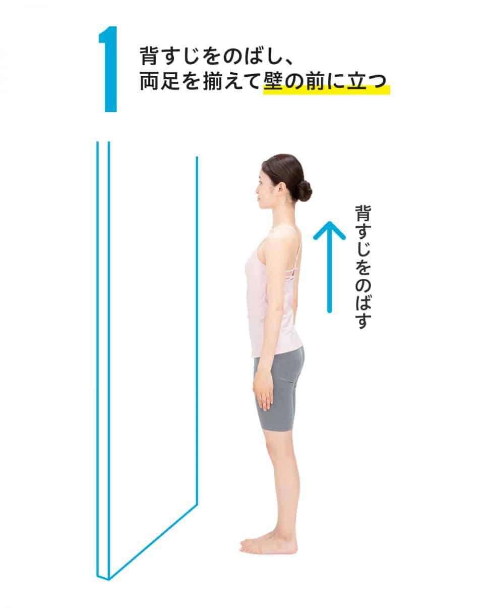 【ひざ裏のばし1】背筋を伸ばし、両足を揃えて壁の前に立つ。