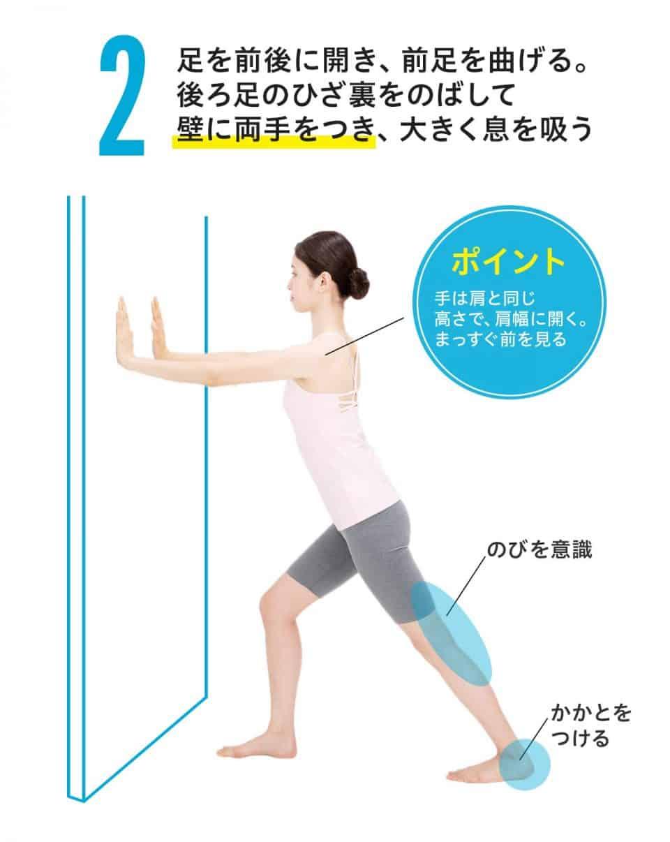 【ひざ裏のばし2】足を前後に開き、前足を曲げる。後ろ足のひざ裏をのばして壁に両手をつき、大きく息を吸う。ポイント:手は肩と同じ高さで、肩幅に開く。まっすぐ前を見る。後ろ足のひざ裏ののびを意識し、かかとは床につける。