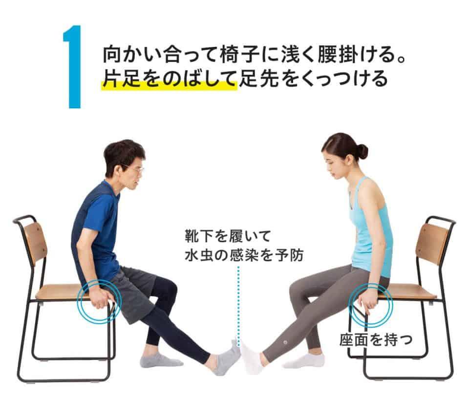 【椅子ひざ裏のばしの方法1】向かい合って椅子に浅く腰掛ける。片足を伸ばして足先をくっつける。靴下を履いて、水虫の感染を予防。手は椅子の座面を持つ。