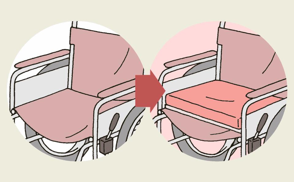 車椅子の乗り心地を改善する方法。車椅子の座面に板を置き、その上に低反発クッションを置く。